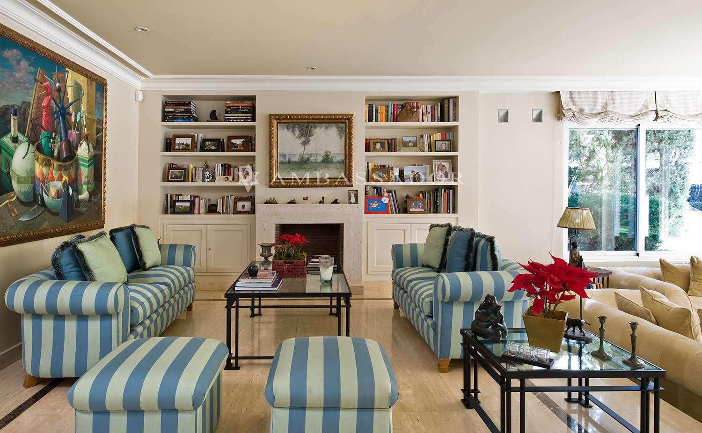 El amplio salón se divide en dos ambientes, separados por un desnivel. Sobre estas líneas podemos ver una de las zonas con una bonita librería y chimenea con embocadura de mármol de color claro