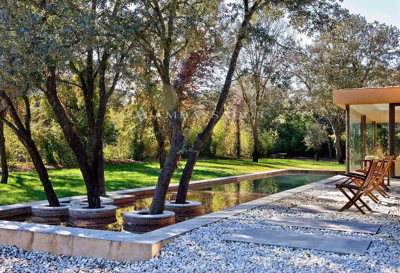 Delante de la fachada sur se encuentra una piscina de diseño que recorre el elegante porche de diseño minimalista