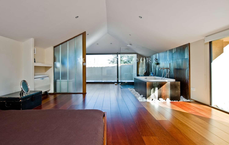 Otra vista del dormitorio principal. Desde esta perspectiva se aprecia mejor como está integrada la zona de la bañera de hidromasaje en el propio dormitorio, creando un espacio continuo entre ambos