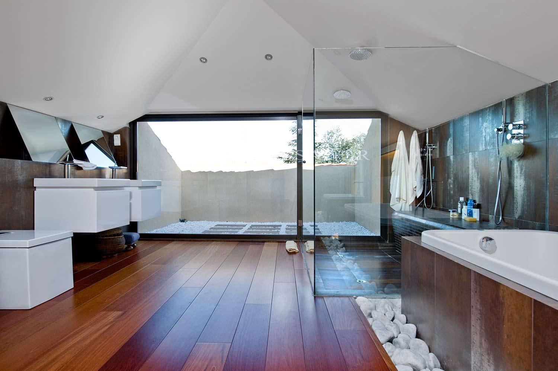 Detalle del baño, en el que destacan, por una parte, la gran cabina de ducha acristalada con espacio para dos personas, y por otra, las originales formas cúbicas de los lavabos, inodoro y bidet