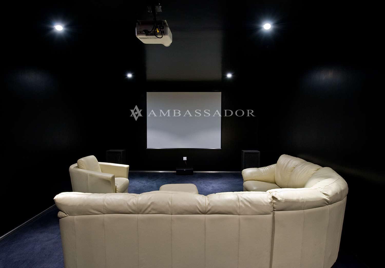 Singular sala de Home Cinema, con equipamiento digno de un estableciemiento comercial: proyector, pantalla de proyeción y sistema de audio surround