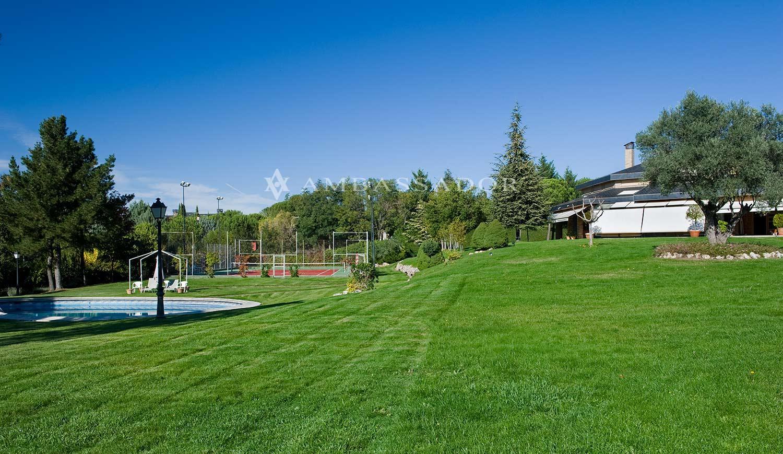 Vista de una zona del amplio jardín con un cuidado césped donde está ubicada la piscina, y al fondo, una pista de tenis