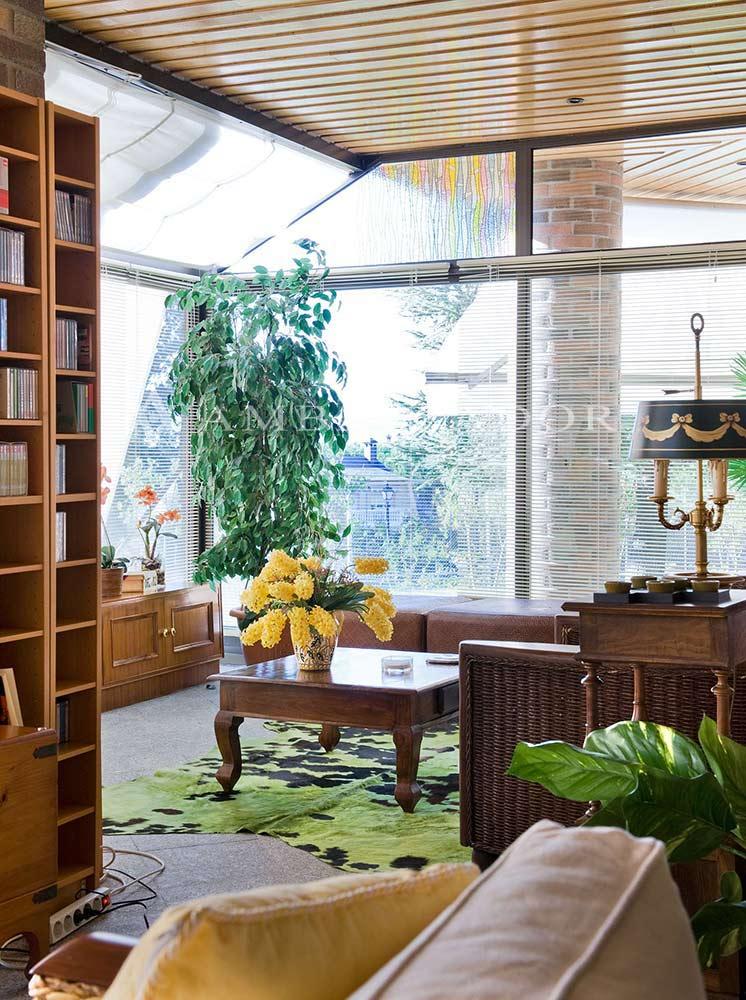 Detalle de una sala de estar acristalada con un ambiente  acogedor y luminoso