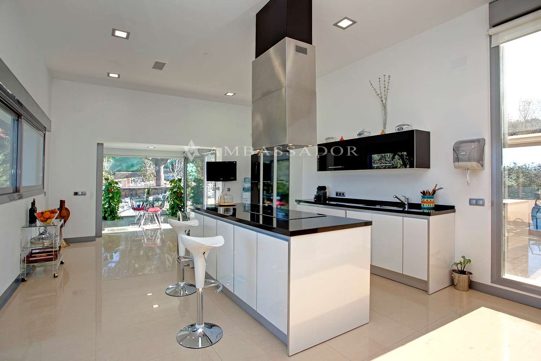 Cocina totalmente equipada con electrodomésticos de última generación, muebles de pulcro diseño, isla central, encimeras en piedra natural de considerable grosor, zona de desayuno y office.