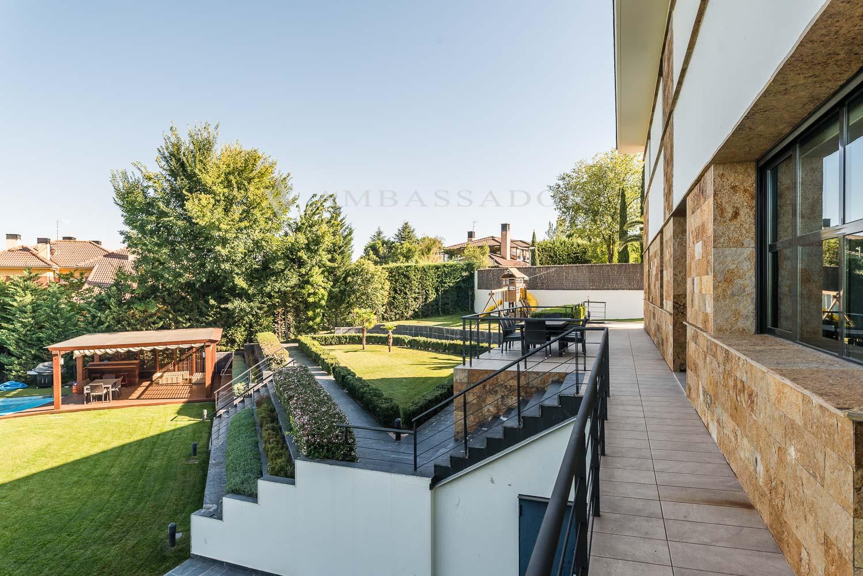 El jardín que se distribuye en diferentes ambientes con la zona de la pisicina y porche, zona de juegos y terraza.