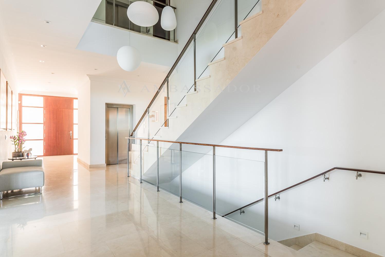 Espectacular hall de entrada con doble altura de techos y bonita escalera de cristal.