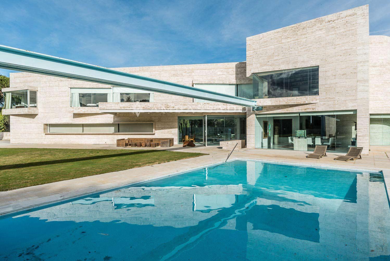 Un amplio porche bajo firme voladizo que da ligereza al edificio, lo continúa y conecta con el exterior, con vistas hacia la estupenda piscina y jardines de la finca.