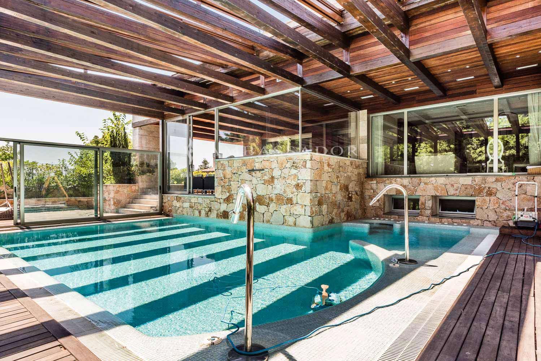 Vista de la piscina que se  halla parcialmente cubierta por una estructura de vigas de madera que dan continuidad a la pérgola que cubre el porche.