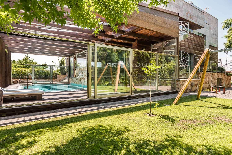 Increíble y majestuoso chalet de original diseño y moderna estética que combina hormigón, revestimientos de madera y grandes ventanales que, en su mayoría, dan acceso a distintas zonas exteriores tales como porche y terrazas