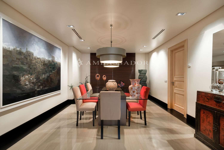 El comedor se articula en torno a un espacio central en el que se ubica la iluminación principal de la sala, así como una mesa minimalista.