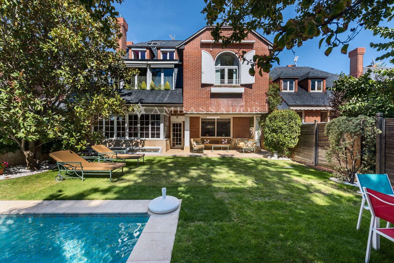 Vista del patio trasero y fachada, en la que se aprecia la piscina y la zona ajardinada.