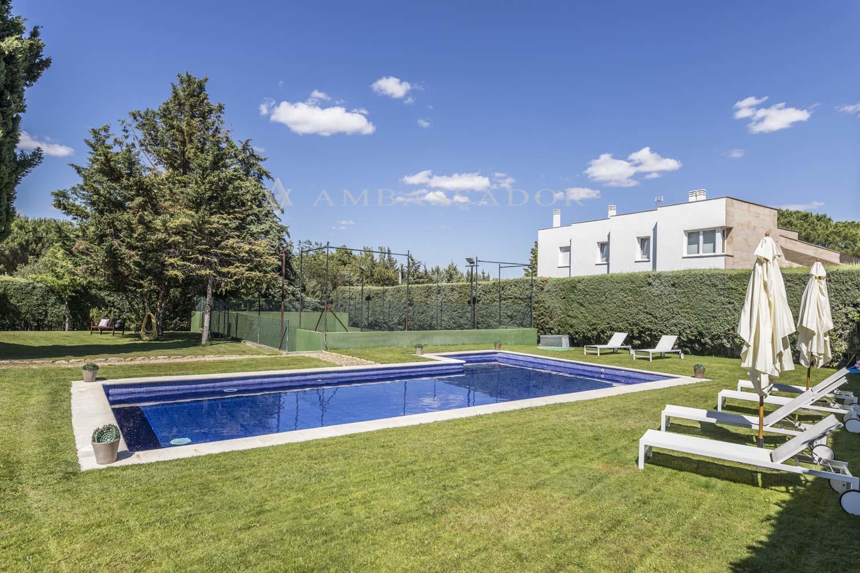 Vista de la piscina, jardín y pista de pádel.