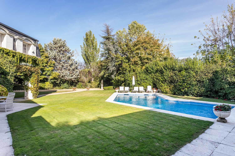 Abradable piscina rodeada de un gran jardín.