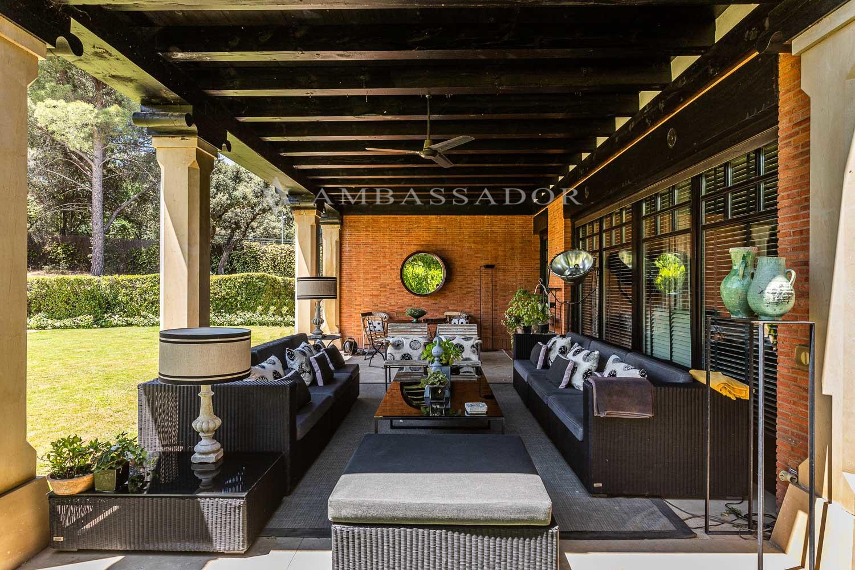 Agradable porche con vistas al jardín y la piscina.