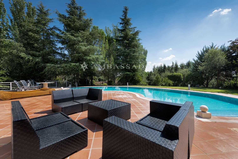 Piscina exterior con zona de terraza con la que se consigue un amplio espacio de ocio, integrado con el propio jardín.