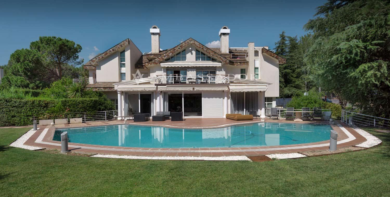 Vista de la fachada posterior del chalet en la que se aprecia la terraza de la piscina, así como la terraza del dormitorio principal.