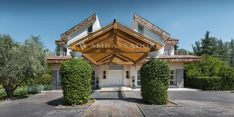 La entrada del chalet se completa con un espectacular recibidor exterior fabricado en madera y cristal.