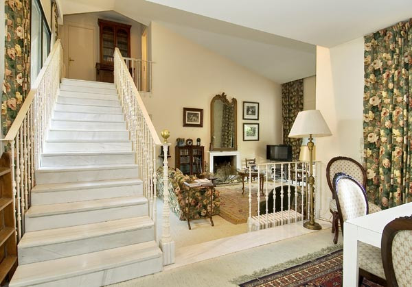 en el lado opuesto de la casa se encuentra una sala de estar y la zona de dormitorios a la que se accede mediante una elegante escalera de forja pintada en