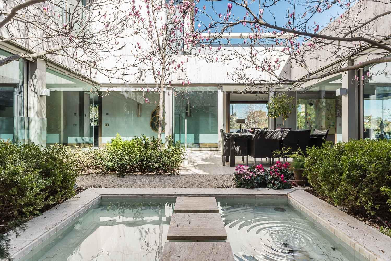Amplio jardín interior con zona cenador y pequeña fuente integrada
