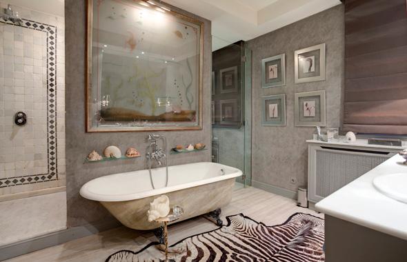 Baño de la suite principal con preciosa bañera con patas en forma de garra. Las paredes están estucadas en pintura plástica de tonos grises.
