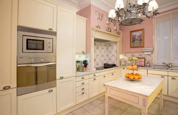 cocina con  muebles de madera lacada en marfil y la encimera en mármol blanco