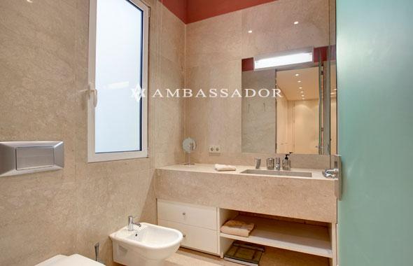 el moderno bao est forrado casi hasta el techo en mrmol de color crema y cuenta con una elegante puerta en cristal esmerilado para su acceso
