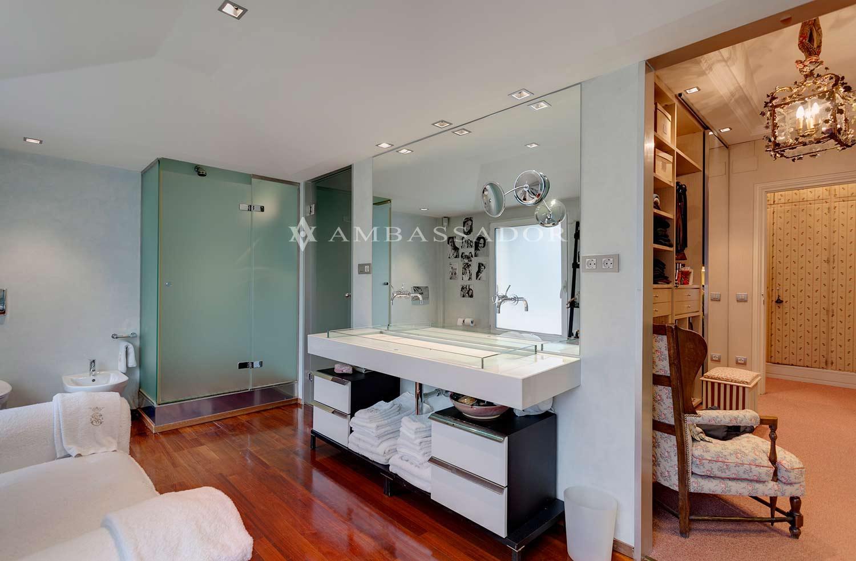 El baño, muy luminoso, cuenta con una gran cabina de ducha y una elegante bañera, encimera volada en Corian sobre la que descansa un exclusivo lavabo de diseño