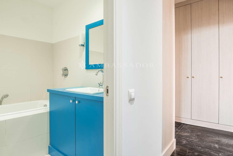El mobiliario lacado en negro brillante de la cocina contrasta con el conjunto clásico de la sala contigua. La isla central hace funciones de mesa de comedor de diario