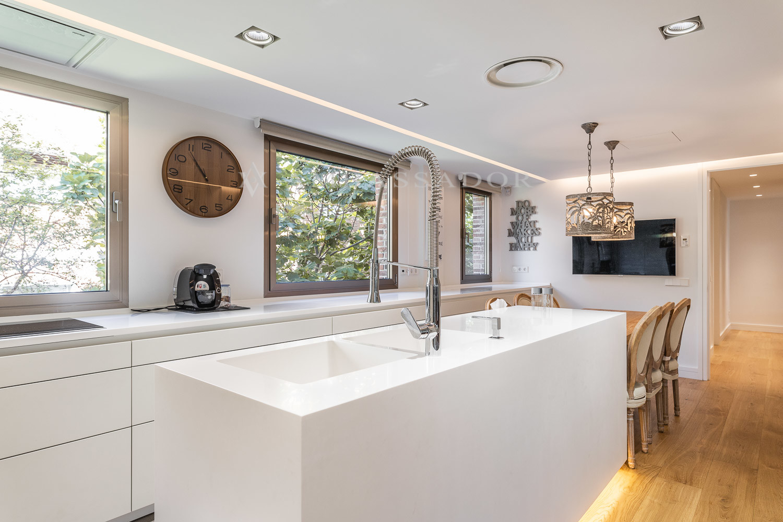 La cocina, con puerta de servicio, está equipada con electrodomésticos Neff, dos neveras Neff integradas, secadora Miele, vinoteca y campana de diseño empotrada en el techo.