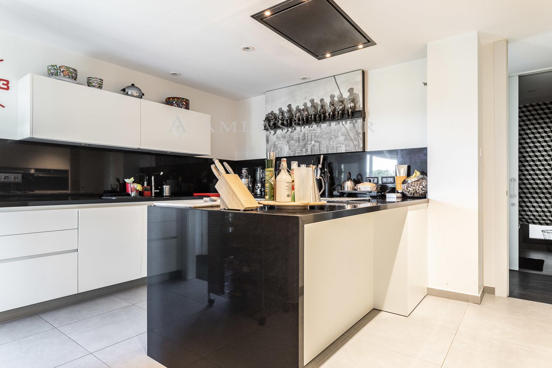 La cocina de diseño está dotada de electrodomésticos de alta gama y grandes espacios de almacenaje realizados a medida.