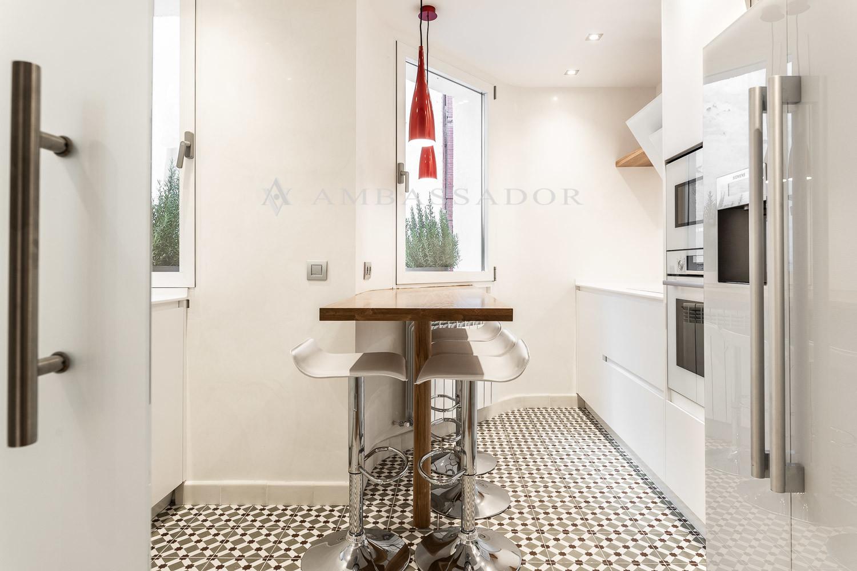 Cocina e diseño con electrodomésticos integrados de alta gama y mesa para cuatro personas.